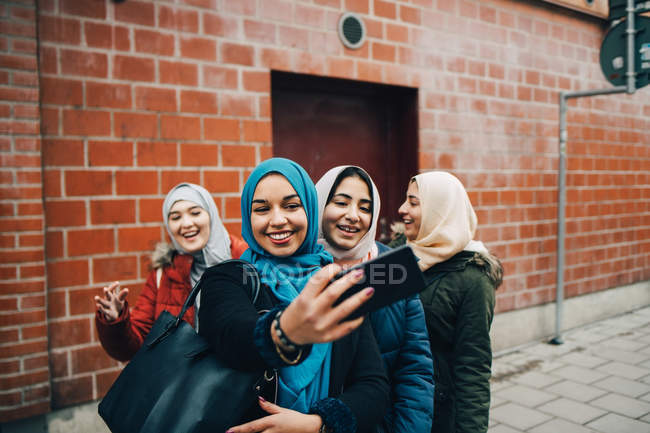Happy young Muslim woman taking selfie with female friends on sidewalk against building in city — Stock Photo