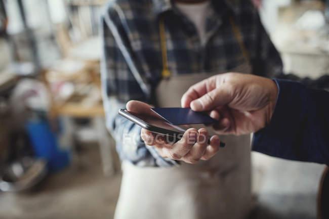Immagine potata del cliente pagare attraverso carta di credito al femmina artigiano — Foto stock