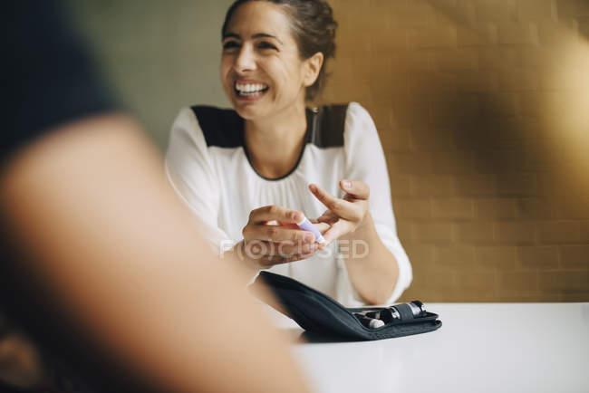 Lächelnde Geschäftsfrau macht Blutzuckertest, während sie mit Kollegin im Büro am Tisch sitzt — Stockfoto