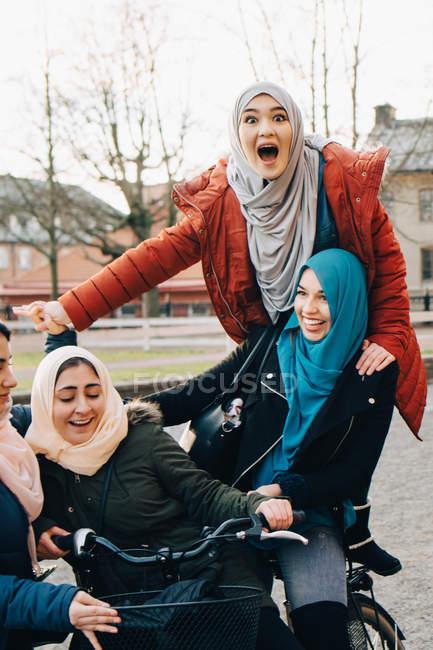 Felices amigos multiétnicos disfrutando con la bicicleta en la ciudad - foto de stock