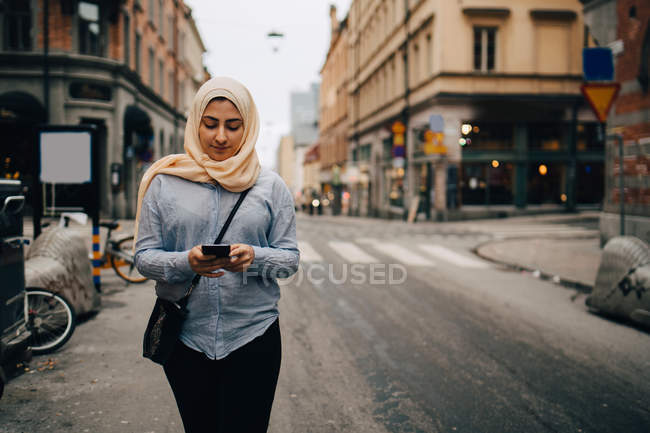 Mujer joven usando el teléfono inteligente mientras camina por la calle en la ciudad - foto de stock