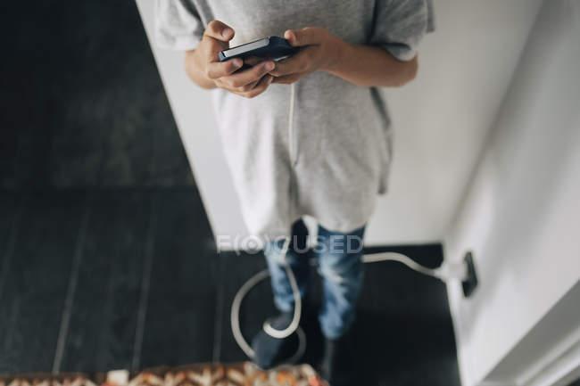 Bassa sezione di ragazzo utilizzando smartphone mentre in piedi in camera a casa — Foto stock