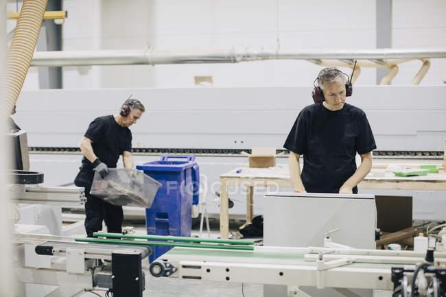 Älterer Mann bedient Maschine in der Industrie, während Mitarbeiter im Hintergrund arbeiten — Stockfoto