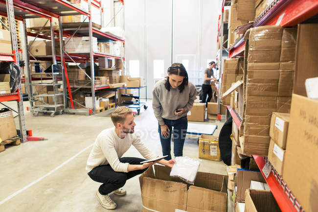 Coworkers examining manufactured objects while using digital tablet at warehouse — Stock Photo