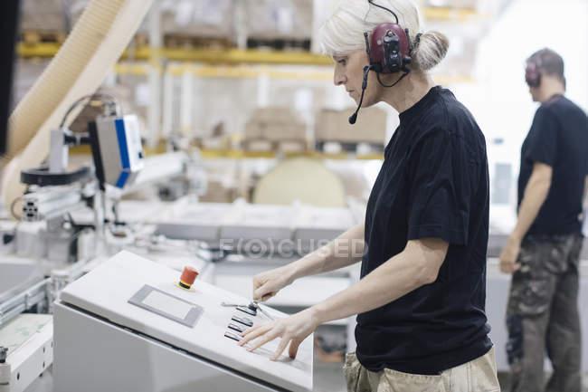 Seitenansicht einer Arbeiterin mit Ohrenschutz, die in der Industrie arbeitet — Stockfoto