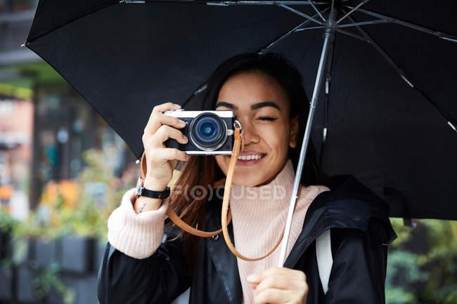 Sorrindo mulher carregando guarda-chuva fotografando através da câmera na cidade — Fotografia de Stock