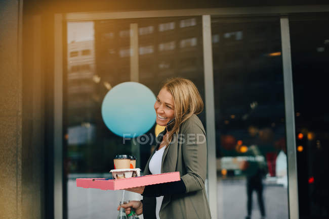 Smiling mature businesswoman talking on smart phone while holding food and drink against cafe in city — Stock Photo