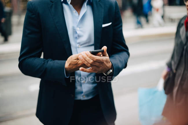 Midsection of mature businessman using smart phone while standing in city — Stock Photo