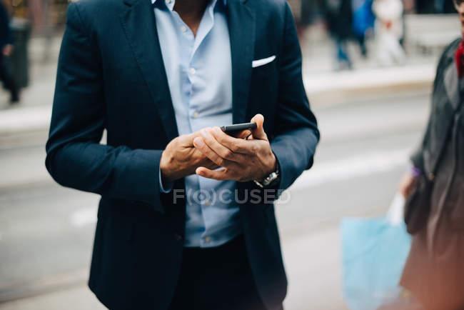 Midsection de hombre de negocios maduro usando el teléfono inteligente mientras está de pie en la ciudad - foto de stock