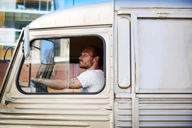 Vue latérale du jeune propriétaire masculin conduisant un camion de nourriture en ville — Photo de stock