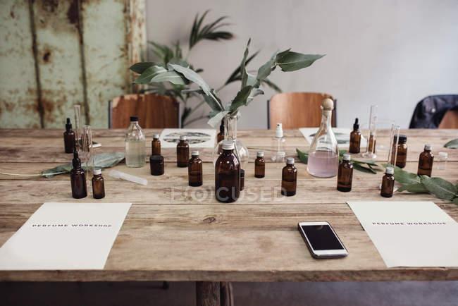 Blick auf das Handy inmitten von Parfümflaschen auf dem Tisch in der Werkstatt — Stockfoto