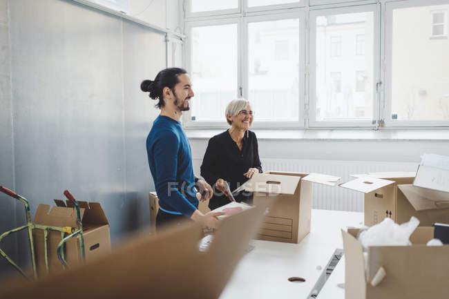 Jeune homme d'affaires souriant avec une collègue féminine déballer des boîtes en carton à table dans un nouveau bureau — Photo de stock