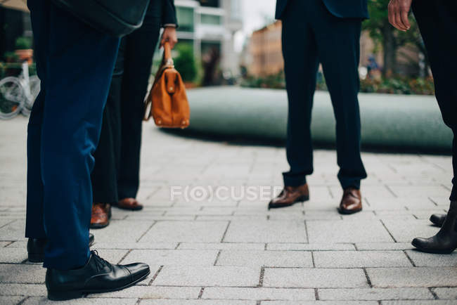Низкая часть деловых людей, стоя на тропу в городе — стоковое фото