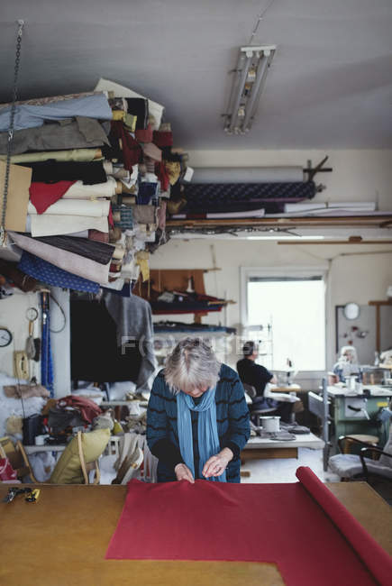 Senior female sewing red fabric while standing at workbench in workshop — Stock Photo