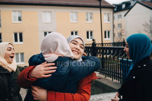 Mujeres musulmanas felices abrazadas por amigos en la ciudad - foto de stock