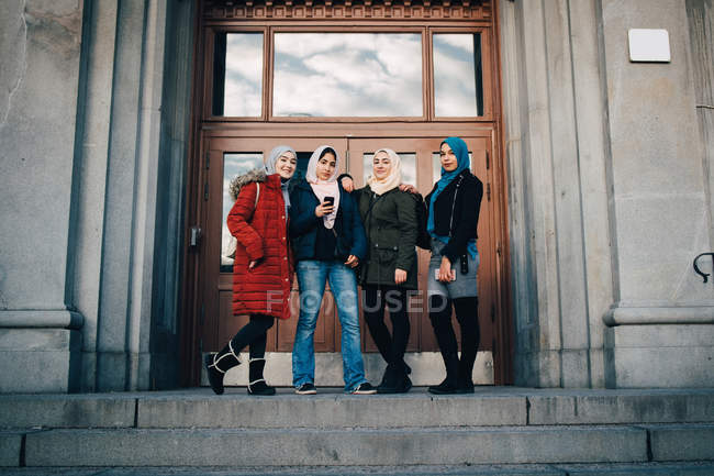 Full length portrait of happy multi-ethnic Muslim friends standing against door — Stock Photo
