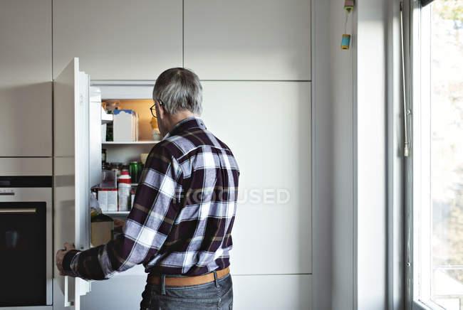 Vista posteriore dell'uomo anziano pensionato in piedi da porta del frigo aperta in cucina a casa — Foto stock