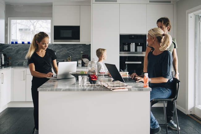 Famiglia in cucina con tecnologie a casa — Foto stock
