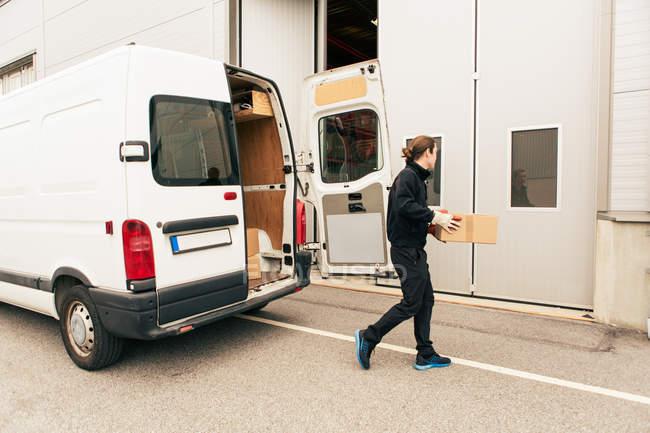 Travailleur masculin avec boîte marchant contre fourgon de livraison sur la route vers l'entrée — Photo de stock