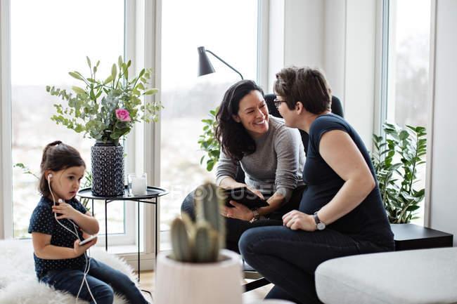 Coppia lesbica che parla mentre la ragazza ascolta musica attraverso il telefono cellulare in soggiorno — Foto stock