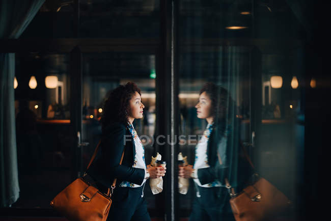 Side view of mid adult businesswoman holding food and drink while walking in cafe — Stock Photo