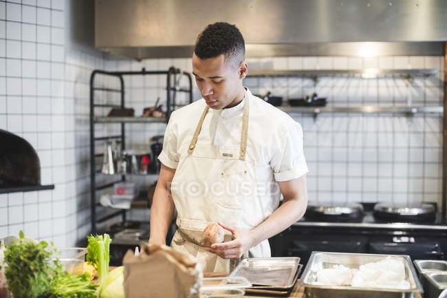 Confident male chef preparing food at kitchen counter in restaurant — Stock Photo