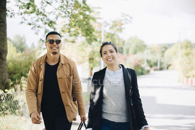 Porträt lächelnder Freunde, die bei sonnigem Wetter auf der Straße in der Stadt reden — Stockfoto