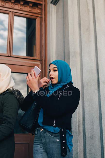 Vista a basso angolo di giovane donna musulmana che applica il rossetto guardando nel telefono cellulare da un amico contro la costruzione — Foto stock