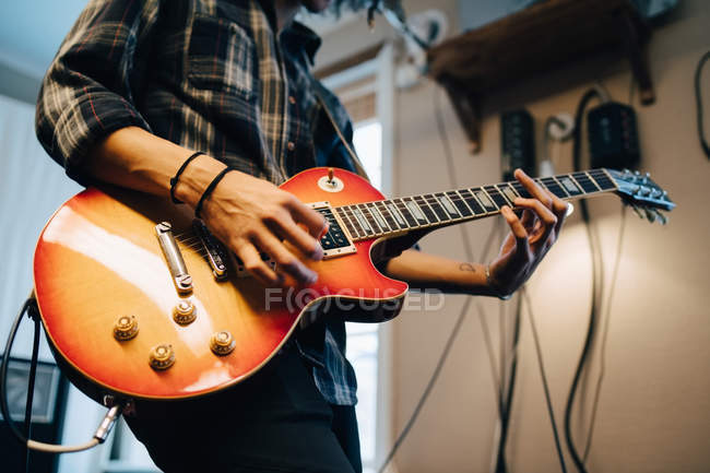 Midsection of man playing guitar while practicing in recording studio — Stock Photo