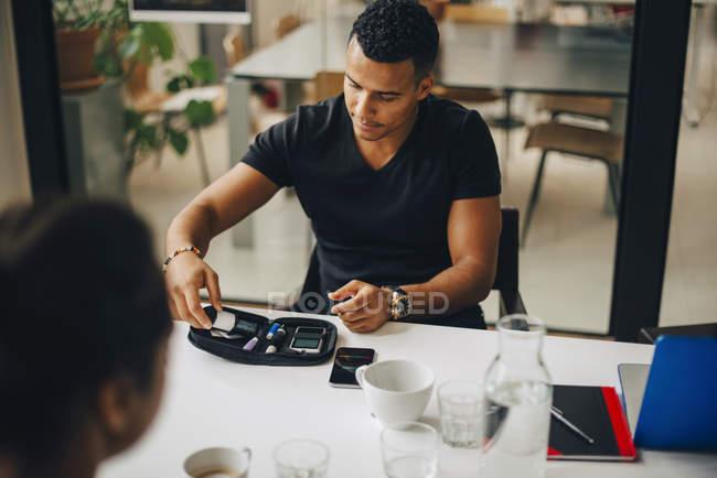 Бізнесмен робить аналіз крові сидячи з колегою за столом — стокове фото