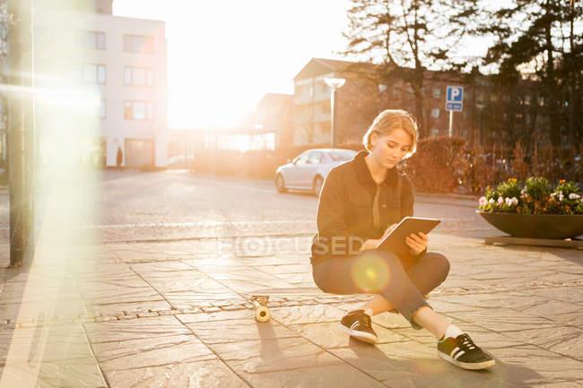 Teenagermädchen benutzt digitales Tablet, während sie an sonnigen Tagen auf dem Skateboard auf dem Bürgersteig sitzt — Stockfoto