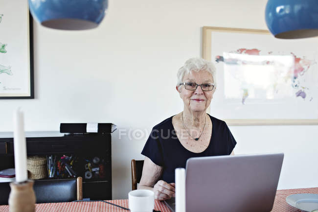 Portrait of smiling retired senior woman sitting with laptop at dining table — Stock Photo
