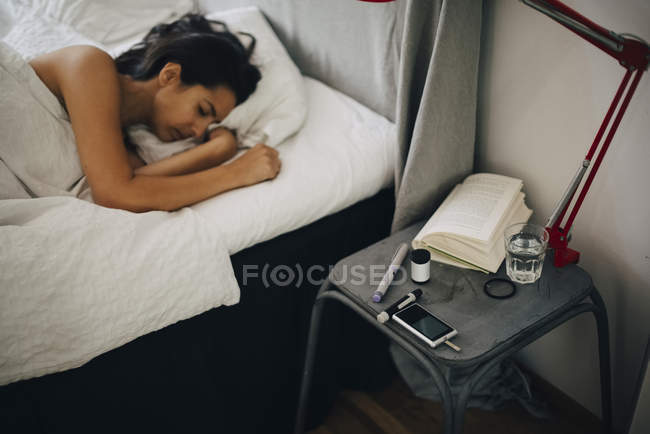 Woman lying on bed by diabetes kit in bedroom — Stock Photo