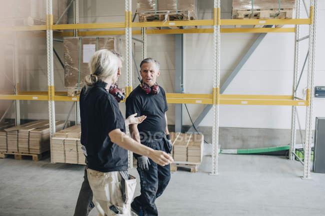 Selbstbewusste Arbeiter und Arbeiterinnen unterhalten sich beim Gang durch die Holzindustrie — Stockfoto