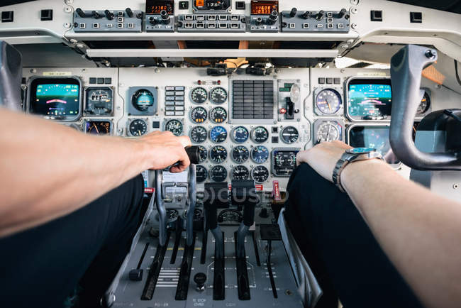 Cropped image of pilots sitting by control panel in cockpit — Stock Photo