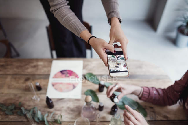 Midsection of young woman holding colleague preparing perfume at table in workshop — Stock Photo