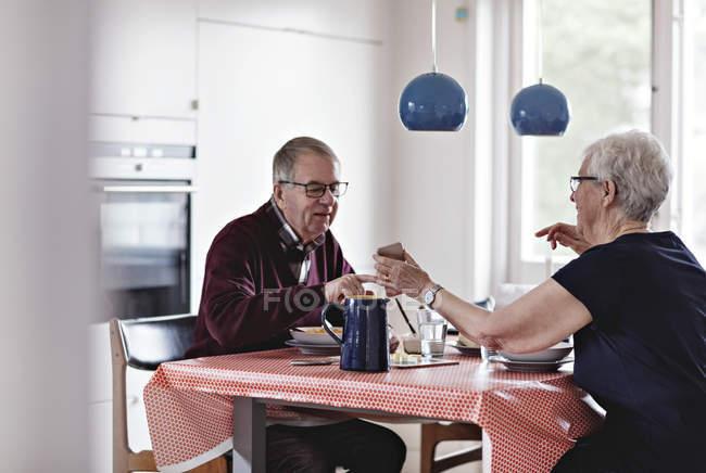 Lunghezza completa della coppia anziana che mangia cibo a tavola — Foto stock