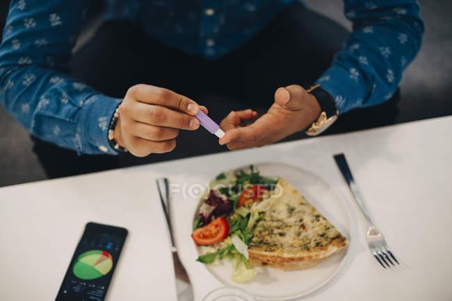 Міделю бізнесмен перевірки рівня цукру крові, а їду в таблиці — стокове фото