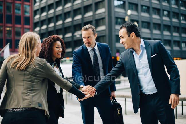 Sorrindo multi-étnica negócios pessoas empilhamento as mãos contra edifício cidade — Fotografia de Stock