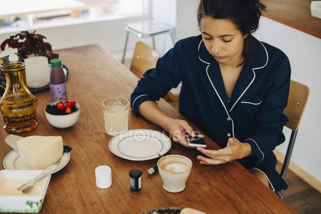 Жінка перевірки рівня цукру крові, маючи сніданок на столі будинку — стокове фото