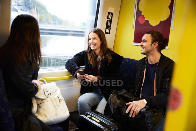 Smiling young friends traveling in yellow train — Stock Photo