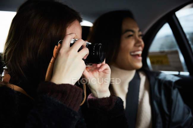 Mulher fotografando através da câmera enquanto sentado com amigo feliz em táxi — Fotografia de Stock