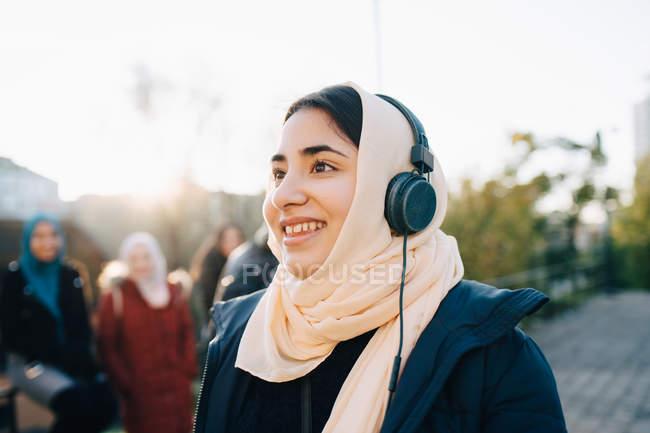 Happy teenage girl listening to headphones looking away against sky — Stock Photo