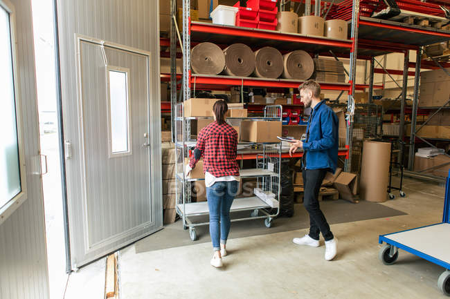 Manual worker looking at female colleague loading boxes on trolley at distribution warehouse — Stock Photo