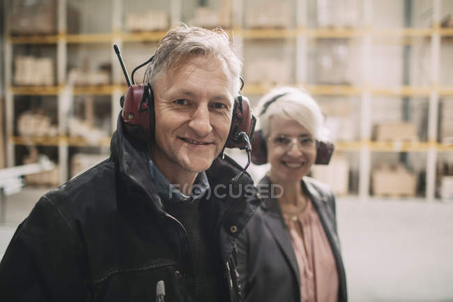 Portrait of smiling businessman with colleague wearing ear protectors at industry — Stock Photo