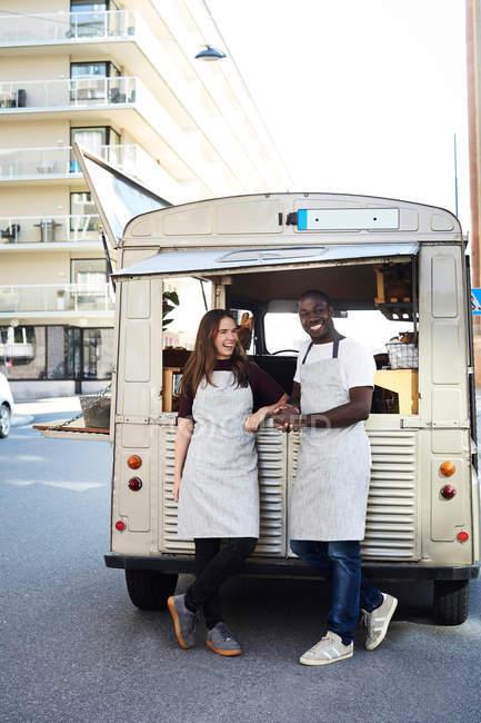 Pleine longueur de souriants propriétaires masculins et féminins debout à l'extérieur camion de nourriture garé sur la rue de la ville — Photo de stock