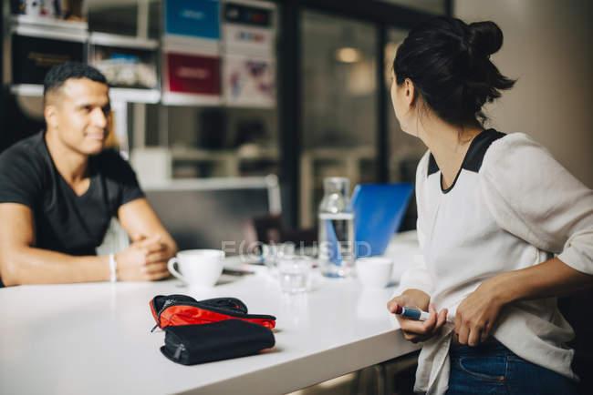 Бізнес-леді ін'єкційні інсуліну під час розмови до колега столом — стокове фото