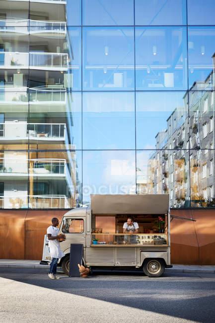 Propriétaires masculins multi-ethniques au camion alimentaire garé sur la rue de la ville contre le bâtiment en verre — Photo de stock