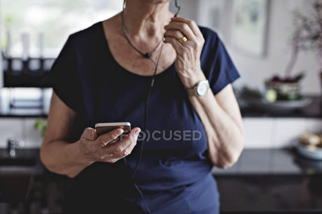 Midsection of senior woman holding smart phone in kitchen at home — Stock Photo
