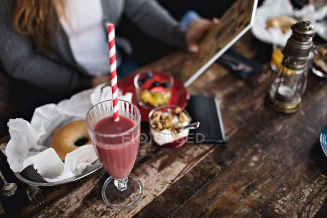 Животик женщина, держащая меню имея бранч обеденным столом в ресторане — стоковое фото
